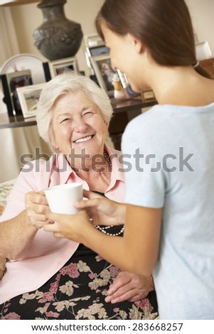 Teenage Granddaughter Making Grandmother Hot Drink At Home