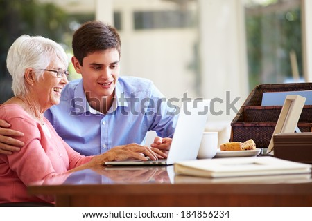 Teenage Grandson Helping Grandmother With Laptop - stock photo