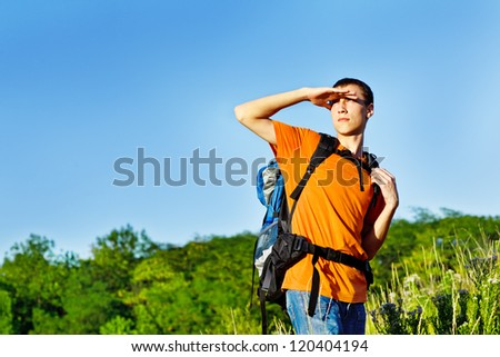 Teenage guy hiking with the backpack - stock photo