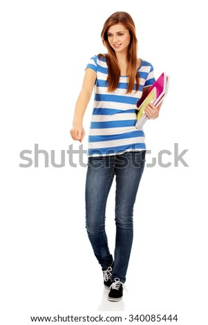 Teenage happy woman holding textbooks and pointing for something.
