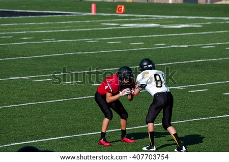 Teenage high school american football boys blocking each other on the field during a game. - stock photo