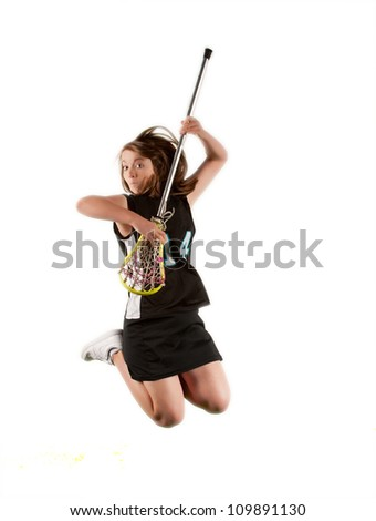 Teenage high school lacrosse player plays her stick like a guitar as she leaps into the air. - stock photo