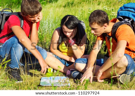 Teenage hikers watching the map - stock photo