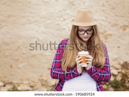 Teenage hipster girl enjoying her take away drink walking down the city street - stock photo