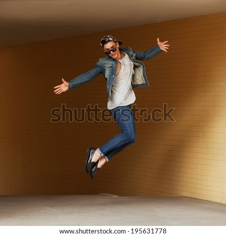 teenage hipster man jumping on the street - stock photo