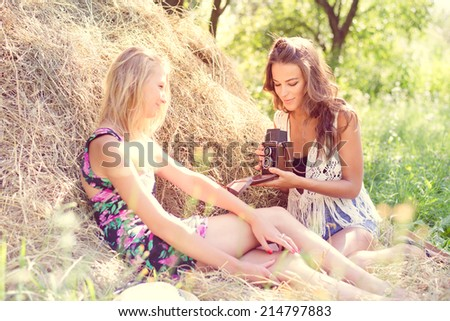Teenage hipster photographer taking picture of female friend on retro film camera on summer day sitting on hay