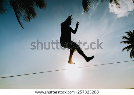 teenage jumping on slackline with sky and sun view on the beach silhouette - stock photo