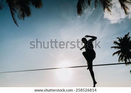 teenage jumping on slackline with sky view on the beach silhouette - stock photo