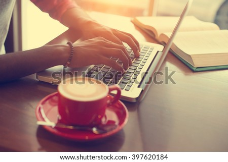 teenage male in cafe with laptop and books in vintage tone