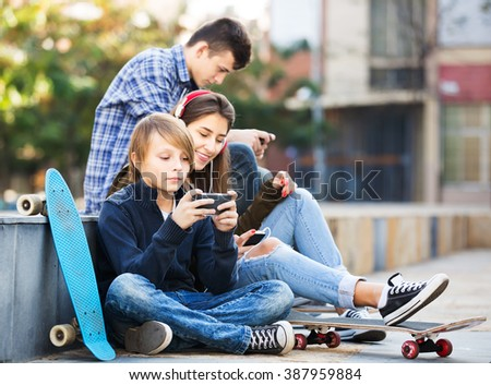 Teenage males and girl relaxing with cell phones in the city - stock photo