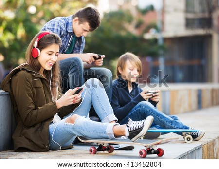 Teenage males and girl relaxing with mobile phones in the city - stock photo