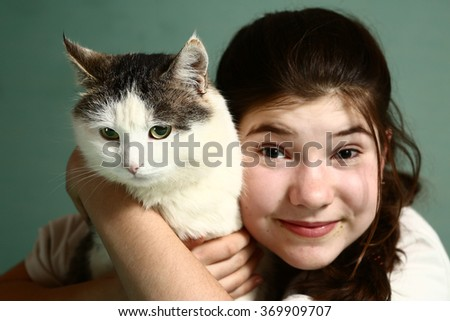 teenage pretty girl with dark long hair hold siberian male cat smiling