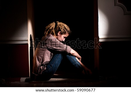 teenage problems. lonely, unhappy, sad girl sitting in a dark, dirty room. - stock photo