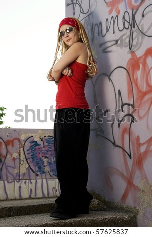Teenage rapper girl standing outdoors at graffiti sprayed wall - stock photo
