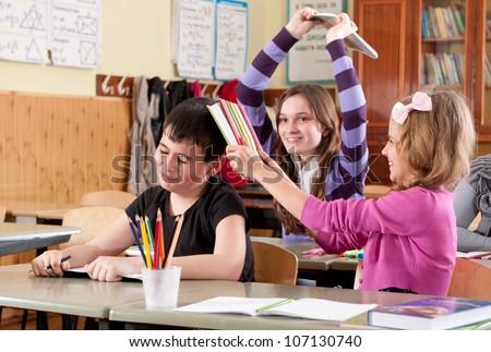 Teenage schoolchildren fighting with books in classroom at school - stock photo