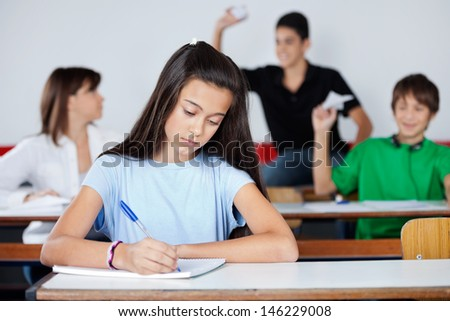 Teenage schoolgirl writing at desk while classmates playing in background