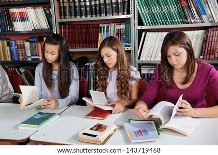 Teenage schoolgirls reading books at table in library
