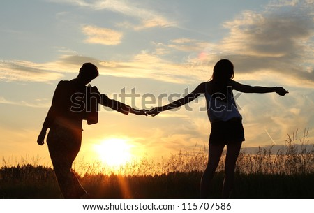 teenage sisters holding hands, silhouettes at sunset