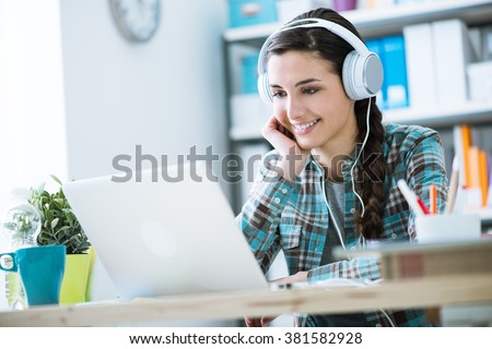 Teenage smiling girl using a laptop and wearing headphones, technology and leisure concept - stock photo