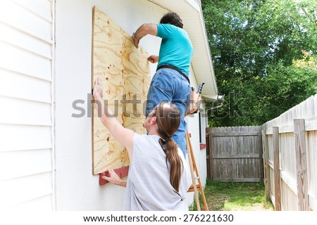 Teenage son helping his father board up the windows of their house in preparation for a hurricane or tornado.   - stock photo