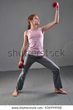 Teenage sportive girl is doing exercises to develop with dumbbells muscles isolated on grey background. Sport healthy lifestyle concept. Sporty childhood. Teenager exercising and posing with weights. - stock photo