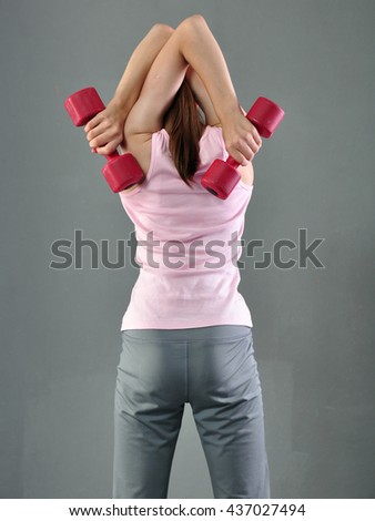 Teenage sportive girl is doing exercises with dumbbells to develop muscles on grey background. Sport healthy lifestyle concept. Sporty childhood. Teenager child exercising with weights. - stock photo