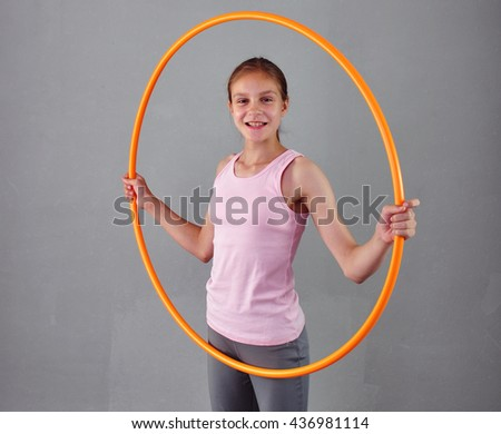 Teenage sportive girl is doing exercises with hula hoop to develop muscle on grey background. Having fun playing game hula-hoop. Sport healthy lifestyle concept. Teenager exercising with tool. - stock photo