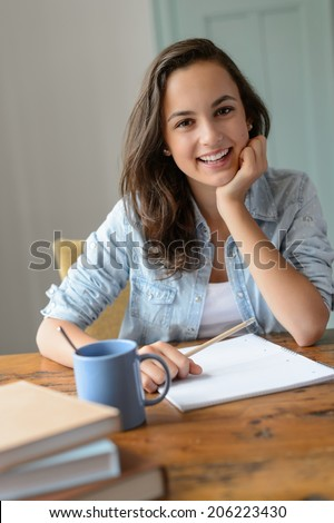 Teenage student girl studying at home smiling leaning against table - stock photo