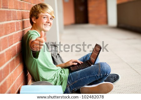 teenage student giving thumb up while using laptop - stock photo