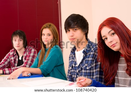 Teenage students in classroom looking at camera - stock photo