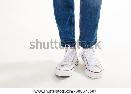 Teenage style. Trendy white sneakers and jeans on women's legs.