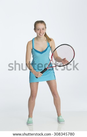 Teenage tennis player posing in her tennis kit with a racket against a plain background. She is smiling for the camera.