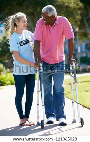 Teenage Volunteer Helping Senior Man With Walking Frame - stock photo