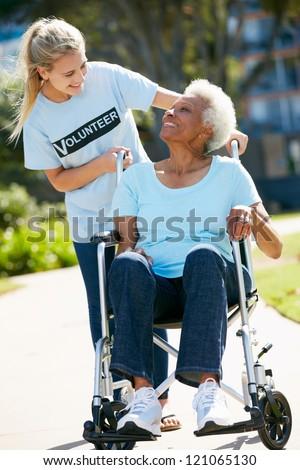 Teenage Volunteer Pushing Senior Woman In Wheelchair - stock photo