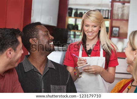 Teenage waitress taking orders from smiling patrons in cafe - stock photo