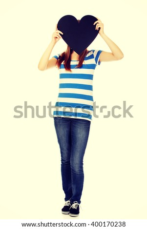 Teenage woman covering her face with paper heart - stock photo