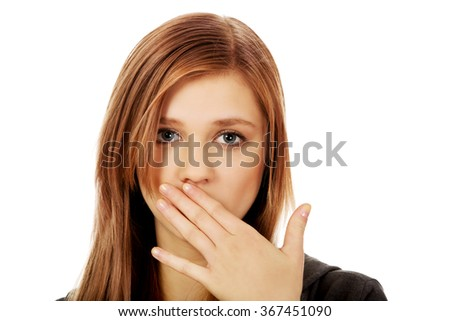 Teenage woman covering mouth with hand - stock photo