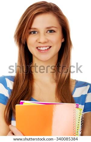 Teenage woman holding a few notebooks. - stock photo