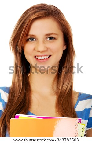 Teenage woman holding a few notebooks