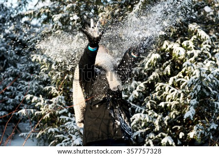 Teenage woman is defending herself from snowball  - stock photo