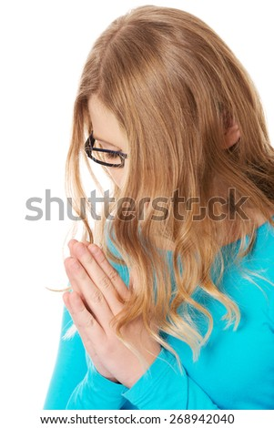 Teenage woman praying with clenched hands - stock photo