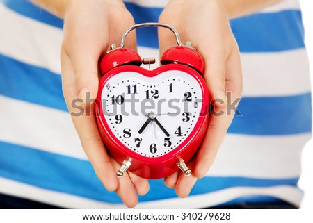 Teenage woman showing alarm clock.