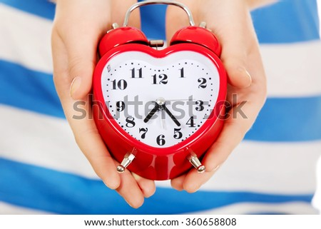 Teenage woman showing alarm clock