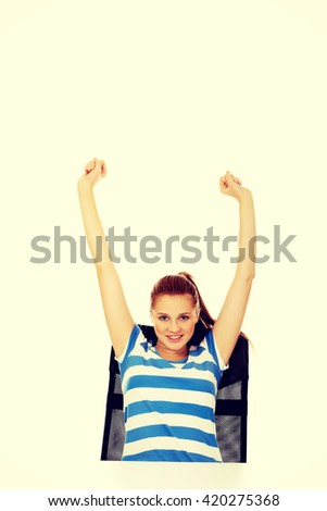 Teenage woman sitting behind the desk with arms up - stock photo