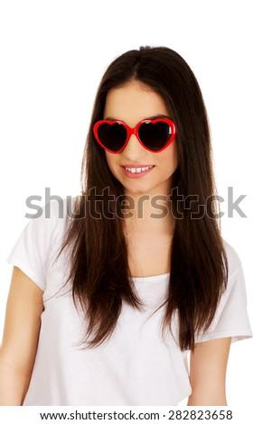 Teenage woman wearing heart sunglasses. - stock photo