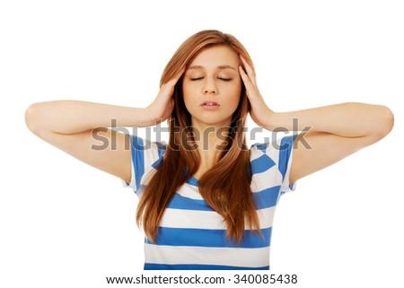 Teenage woman with headache holding her hand to the head. - stock photo
