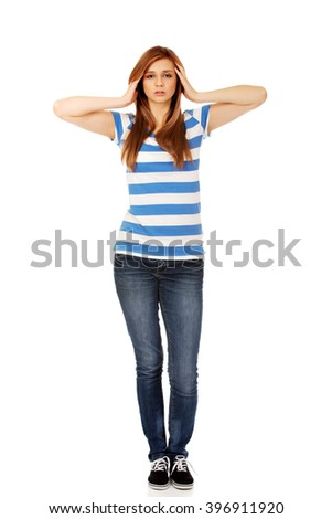 Teenage woman with headache holding her hand to the head