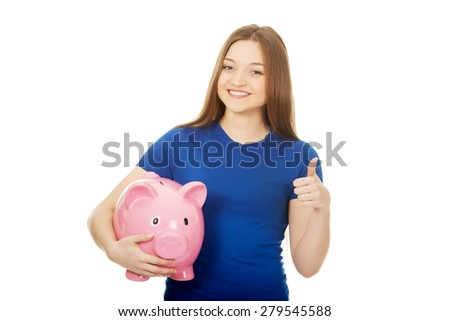 Teenage woman with piggybank and thumbs up. - stock photo