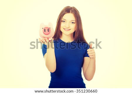 Teenage woman with piggybank and thumbs up. - stock photo