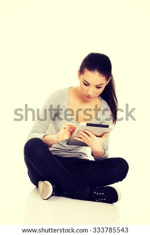 Teenage woman with tablet sitting cross legged.
